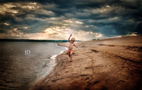 Малыш, северная река и грозовое небо